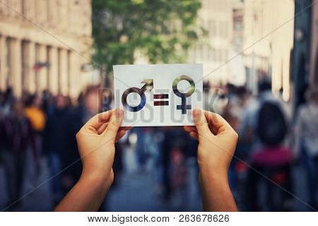 poster of Gender equality concept as woman hands holding a white paper sheet with male and female symbol over a crowded city street background. Sex sign as a metaphor of social issue.
