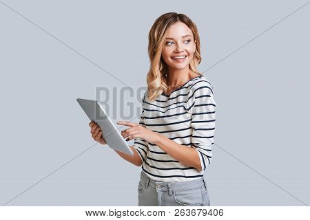 Examining Her New Digital Tablet. Attractive Young Woman Smiling And Using Her Digital Tablet While