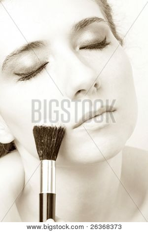 closeup of woman applying loose powder with thick black brush