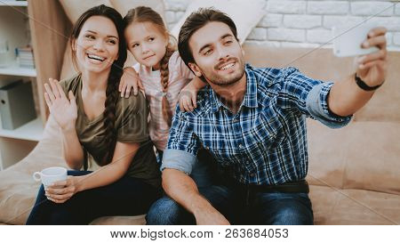 Happy Family. Parents And Daughter. Family Spends Time Together. Happy Child And Parents. Brown Sofa