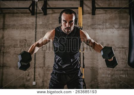Young Muscular Man Doing Hard Exercise With Dumbbells For Shoulders On Hard Training At The Gym.