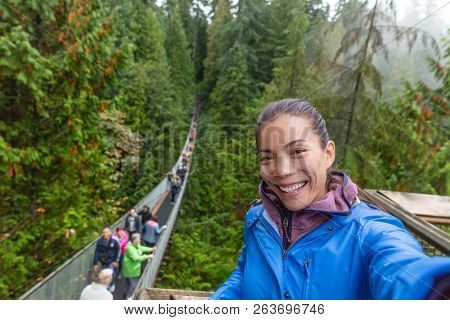 Canada travel tourist woman taking selfie photo at Capilano Suspension Bridge in Vancouver, British Columbia, canadian vacation destination for tourist. Asian girl talking to camera phone.