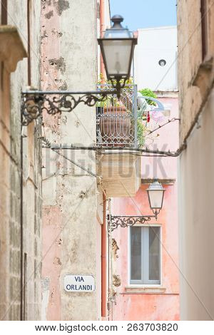 Specchia, Apulia, Italy - Lanterns And A Balcony In A Historic Alleyway