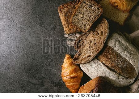 Variety of fresh baked rye, spelled, wheat craft artisan bread, whole and sliced, on cloth over black texture background. Flat lay, space poster