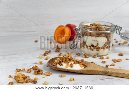 A  Jar Filled With Granola And Yogurt, Wooden Spoon Whit Granola And Apricot On White Wood Table