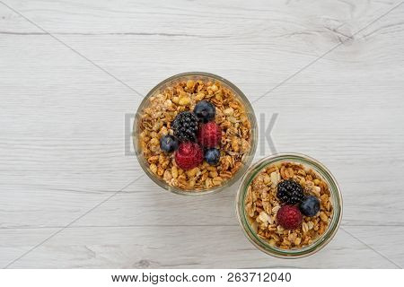 Two Jars Full Of Granola  Whit Berries On The White Wood Table, Top View