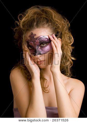 portrait of mysterious blond woman wearing purple stylish carnival mask; role play