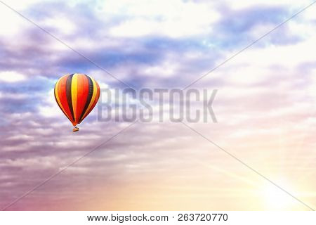 Balloon ride at sunrise. A colourful hot air balloon  in the early morning sky. Space for text.