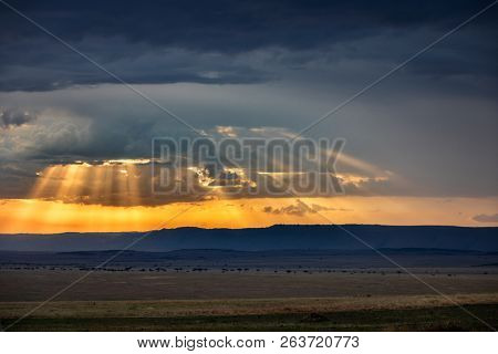 The plains and acacia trees of the Masai Mara, Kenya, and the Siria or Oloololo Escarpment at dusk.