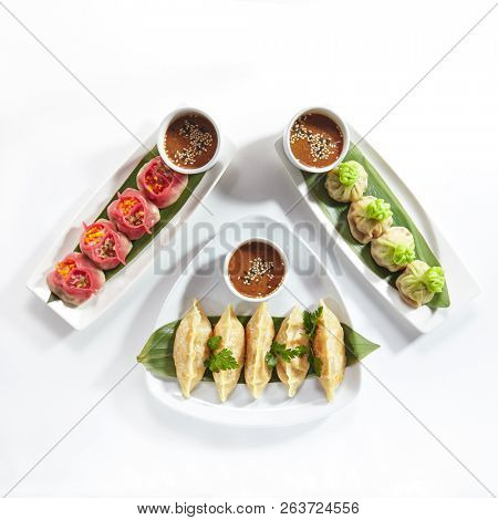 Set of Various Chinese Dim Sum, Gyoza, Jiaozi or Momo on a Banana Leaves with Spicy Sauces Top View. Dimsum Collection or Buffet with Greens and Spices Isolated on White Background