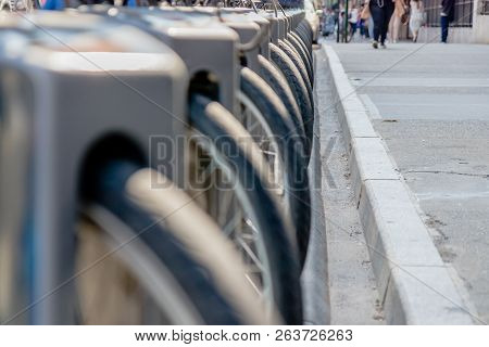 Close-up Of Bike Tire Parked In Bikes Docking Station. Row Of Bikes For Rent At Docking Stations In