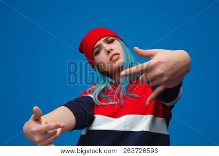 From below shot of modern hip-hop trendy woman showing rock-and-roll gesture and looking provocatively at camera poster