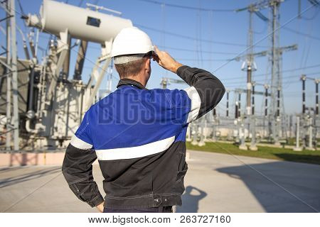 Electrician Engineer On Power Electric Station Look At Industrial Equipment. Technician In Helmet On