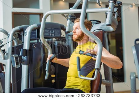 Portrait of a handsome bodybuilder smiling and looking at camera while exercising at a modern fitness machine for pectoral fly and deltoid workout