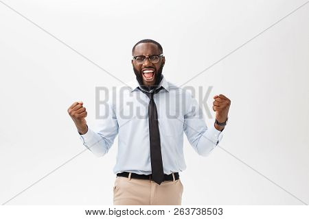 Happy African Businessman Wearing A Corporate Grey Shirt And Black Tie Punching The Air With His Fis