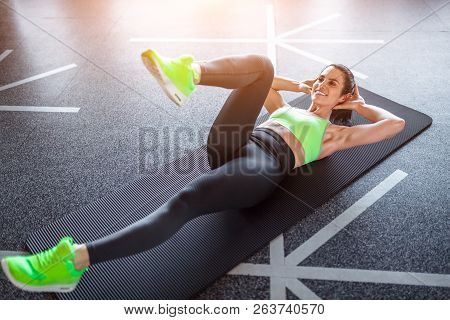 From Above Shot Of Attractive Adult Lady In Sportswear Lying On Floor And Doing Exercise During Work