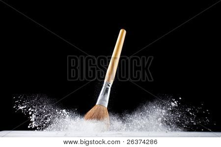 thick professional brush and loose white powder particles scattered around