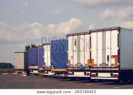 Modern Trucks Of Various Models Are In A Row On Truck Stop. Back View.
