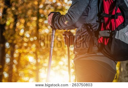 Fall Foliage Trailhead. Caucasian Men With Backpack And Nordic Walking Poles On The Scenic Trailhead