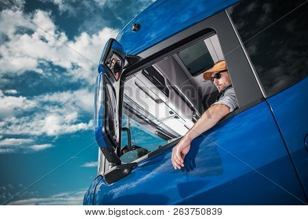 Heavy Load Cargo Delivery. Caucasian Truck Driver Inside Semi Tractor Cabin And The Blue Sky. Transp