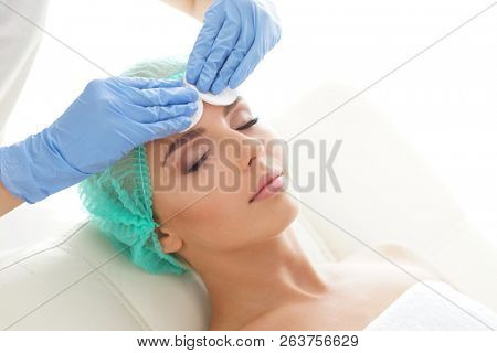 Cosmetologist cleaning face of a young woman with a cotton pads. Removing cosmetics with hygienic discs.