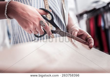 Close Up Of Hands Of Fashion Designer Wearing Stylish Accessories Cutting Fabrics