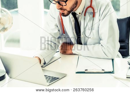 Doctor Working On Laptop Computer Hospital.