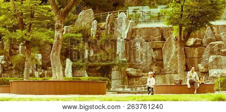 Samcheok, South Korea; September 24, 2018: Young Unidentified Korean Woman On Park Bench As Her Chil
