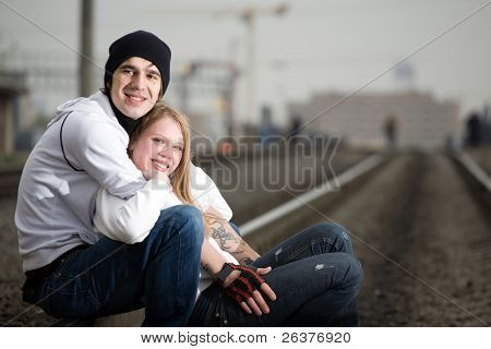 Young couple sitting on railway tracks and smiling.