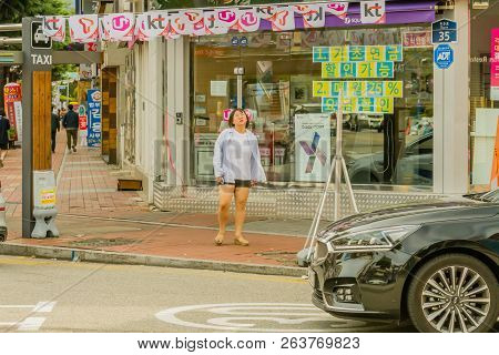 Samcheok, South Korea; September 24, 2018: Young Unidentified Korean Woman Walking  In Front Of Cell