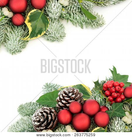 Christmas background border with red bauble decorations, holly berries, snow covered spruce pine, ivy, pine cones and mistletoe on white background with copy space.