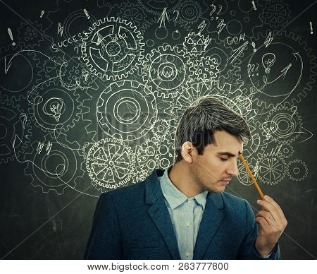 Hard Thinking Serious Man Over Blackboard Background Gear Brain Arrows And Mess As Thoughts. Concept