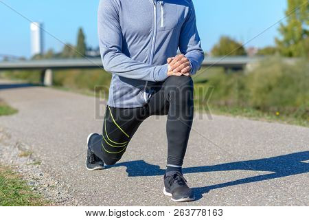 Unidentifiable Senior Adult Man Wearing Sportswear Stretching In Park On Sunny Day