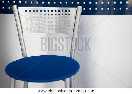 Metal bar chair with square holes. Modern background.