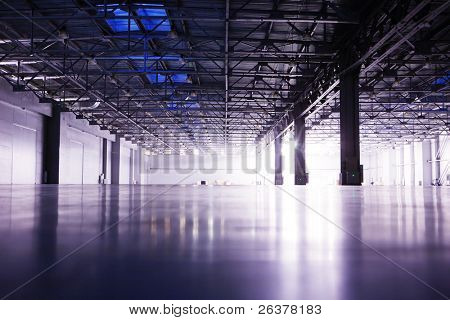 Modern empty storehouse with lights at far side