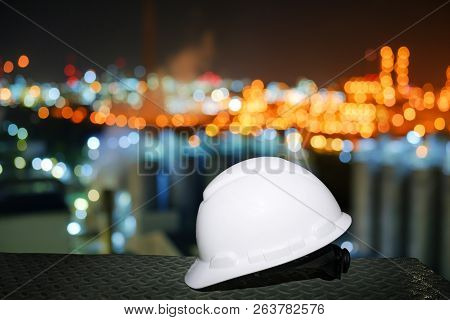 White Safety Helmet On Blurred Lights Industrial Plant Background, Worker At Night Concept In Petroc