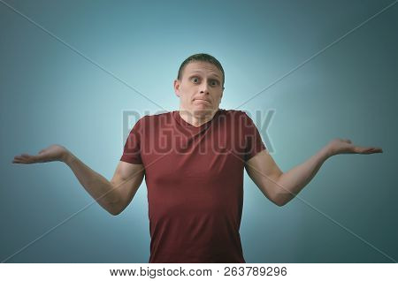 Guilty Man Is Standing And Is Shrugging His Shoulders Isolated On Blue Background.
