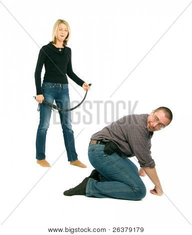 A man is sitting on his haunches and a woman is standing behind him with a belt in her hand.