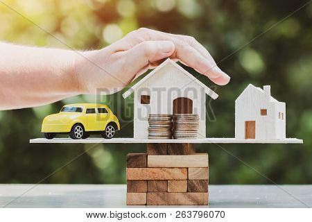 Business Real Estate Investment Concept : Hands Protect Wooden Home, Car Model With Money Coin Placi