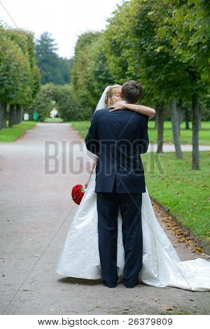 Full-length picture of kissing on the path in the park, the groom is standing with his back to the camera