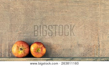 An image of a wooden background with two small apples