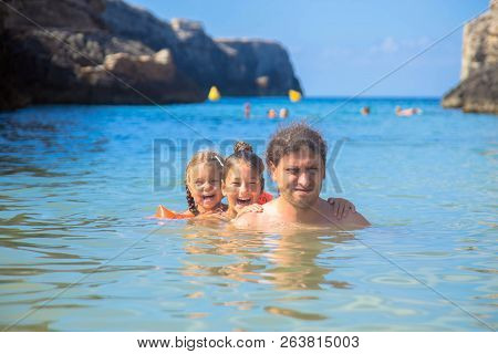 Happy Family Swim And Play In The Sea. A Father And Two Daughters Are Having Fun On The Beach. Dad A