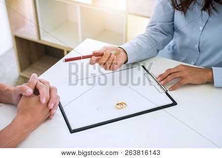 Husband And Wife Are Reading Divorce Agreement And Filing Pen To Signing Decree Of Divorce (dissolut