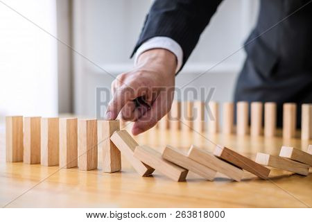 Wooden Game Strategy, Businessman Hand Stopping Falling Wooden Dominoes Effect From Continuous Toppl