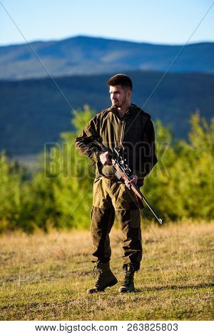 Hunter khaki clothes ready to hunt hold gun mountains background. Hunter with rifle looking for animal. Hunting shooting trophy. Mental preparation for hunting individual process. Man rifle for hunt poster