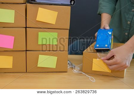 Startup Small Business Owner Packing Cardboard Box At Workplace. Freelance Woman Entrepreneur Seller