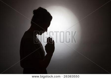 Silhouette of praying woman