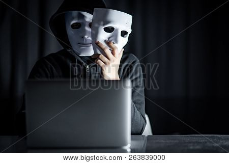 Mystery Male Hoodie Hacker Wearing Mask Holding White Mask Sitting With Laptop Computer On The Table