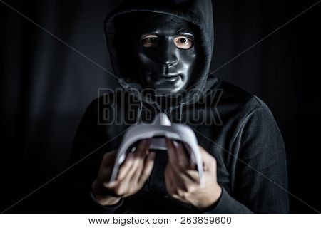 Mystery Hoody Man Wearing Broken Black Mask Holding White Mask. Anonymous Social Masking. Major Depr
