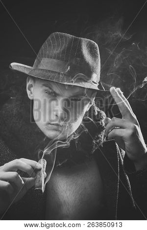 Vintage Detective Concept. Man In Coat, Hat Smoking Cigar, Dark Background. Guy In Old Fashioned Out